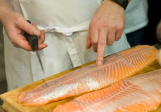 Cook preparing fresh salmon fish Stock Photo