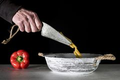 Hand pouring pasta, penne, in white vintage bowl royalty free stock image