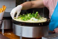 Cook preparing vegetarian pancake royalty free stock images