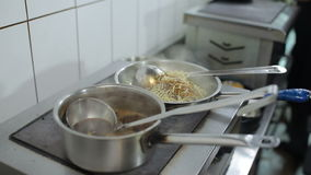 Cook prepearing a dish in the restaurant. The man waters the dish on the stove a some sauce stock footage