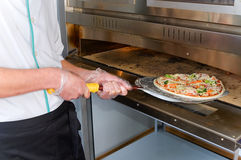 The cook pulls out a ready pizza from the furnace Stock Photo