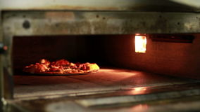 Cook Pulls A Pizza Out Of The Oven. Royalty Free Stock Image