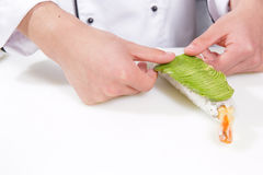Cook puts avocado on sushi roll Royalty Free Stock Image