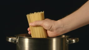 Cook puts down a bunch of spaghetti in a steel pot stock video footage