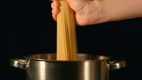 Cook puts down a bunch of spaghetti in a steel pot Stock Image