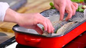 The cook puts the fish in a baking dish stock footage
