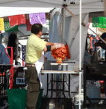 Cook puts meat on rotisserie at vendor's tent Royalty Free Stock Image
