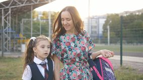 Mother is walking little girl in a school uniform to school. Mother and daughter together holding hands going to school. stock footage