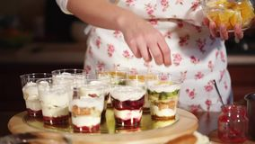 The cook puts pieces of fruit inside the cups with cream decorating with oranges. Close up shot of the sweet desserts that are on the tray, the cook puts the stock video footage