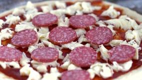 The cook puts salami in pizza. Close-up. Prepares pizza. The cook puts salami in pizza. Close-up. Dough, Sauce, Salami and Mozzarella stock video footage