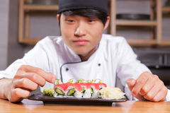 Cook puts seaweed on sushi Stock Images