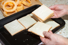 Cook puts toast bread into roasting pan Royalty Free Stock Photo