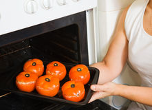 Cook  putting farci tomato into oven Royalty Free Stock Image