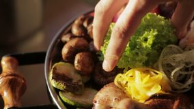 Cook putting lettuce leaves on the plate with the hot shish kebab and roasted vegetables stock video