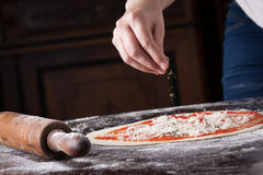 Cook putting oregano on raw pizza Stock Images