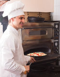Cook putting pizza to bake in oven Royalty Free Stock Photo