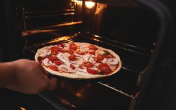 Cook ręka immerses pizzę w piekarniku obraz royalty free
