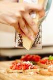 Cook ręki uciera parmesan nad pomidorowymi bruschettas Obrazy Stock