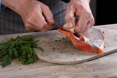 Removing skin from salted salmon Royalty Free Stock Photos