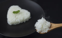 Cook rice serve with heart shape on black dish with smoke. And ears of rice Royalty Free Stock Image