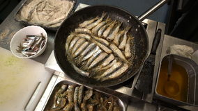 Cook roasts fresh smelt in the fish restaurant. Close-up stock video