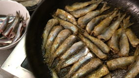 Cook roasts fresh smelt in the fish restaurant. Close-up stock video footage