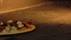Cook rotates the pizza with olives and ham inside the oven stock footage