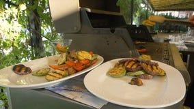 Cook rozkładał na talerzach z pomocą forceps różnorodni warzywa tak jak oberżyna, pieprz, zucchini i pieczarki, Zdrowy zbiory wideo
