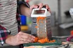 The cook rubs carrots on a grater, a kind from the first person stock photo