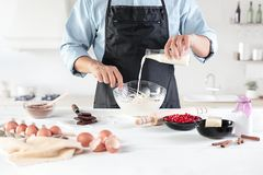 A cook with eggs on a rustic kitchen against the background of men`s hands Royalty Free Stock Photos