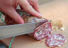 Cook's hand slicing the salami Royalty Free Stock Images