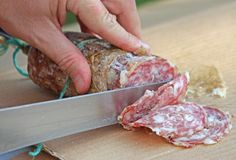 Cook's hand slicing the salami Royalty Free Stock Image