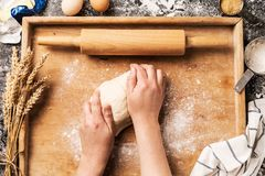 Cook`s hands kneading the raw dough pastry on board Stock Photo