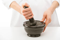 Cook's hands pounding something using mortar and pestle Royalty Free Stock Images
