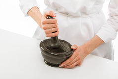 Cook's hands pounding something. Using mortar and pestle, closeup shot Stock Photos