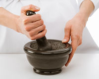 Cook's hands pounding something using mortar and pestle Royalty Free Stock Photography