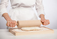 Cook's hands rolling out dough Royalty Free Stock Images