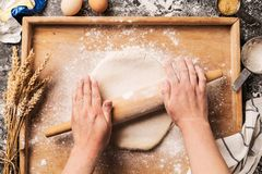 Cook`s hands rolling out the raw dough pastry on board Stock Photos