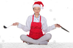 Cook in Santa Claus hat, yoga, knives and snow Stock Images