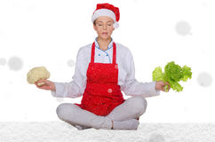 Cook in Santa hat, yoga, vegetables under snow Stock Photography
