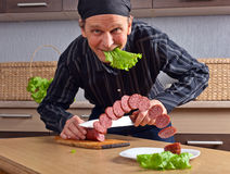Cook and sausage Royalty Free Stock Image