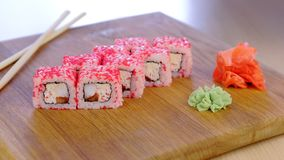 Cook serves rolls with fish, shrimps and red caviar on top on wooden board with wasabi. Cook serves rolls with fish, shrimps and red caviar on top on wooden stock footage