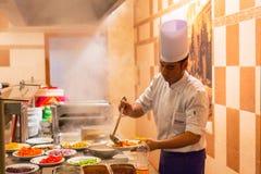 Cook serving dinner in egyptian resort. HURGHADA, EGYPT - APR 9, 2013: Cook serving dinner at Three Corners Sunny Beach hotel in Hurghada. Three Corners is Royalty Free Stock Image