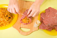 Cook sewing stuffed beef by toothpicks Royalty Free Stock Photos