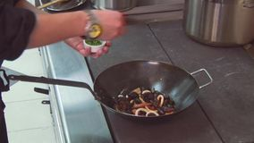 Cook shake wok frying pan with mussels, prawns on stove, add pepper, basil. Restaurant kitchen. stock video