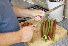 Cook sharpening knife over chopping board Stock Photography