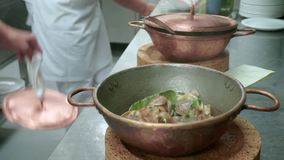 A cook showing clams in copper pot covered with lid. A cook showing clams with garlic in copper pot covered with lid stock footage
