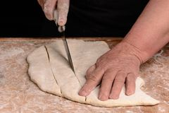 The cook slicers raw dough with a knife on a narrow line. 2018 Stock Photo