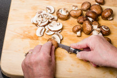 Cook slicing mushrooms in kitchen Royalty Free Stock Images