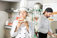 Cook Smelling Aroma Of Healthy Food. Attractive female chef enjoying the aroma of freshly prepared food in kitchen at restaurant stock photo